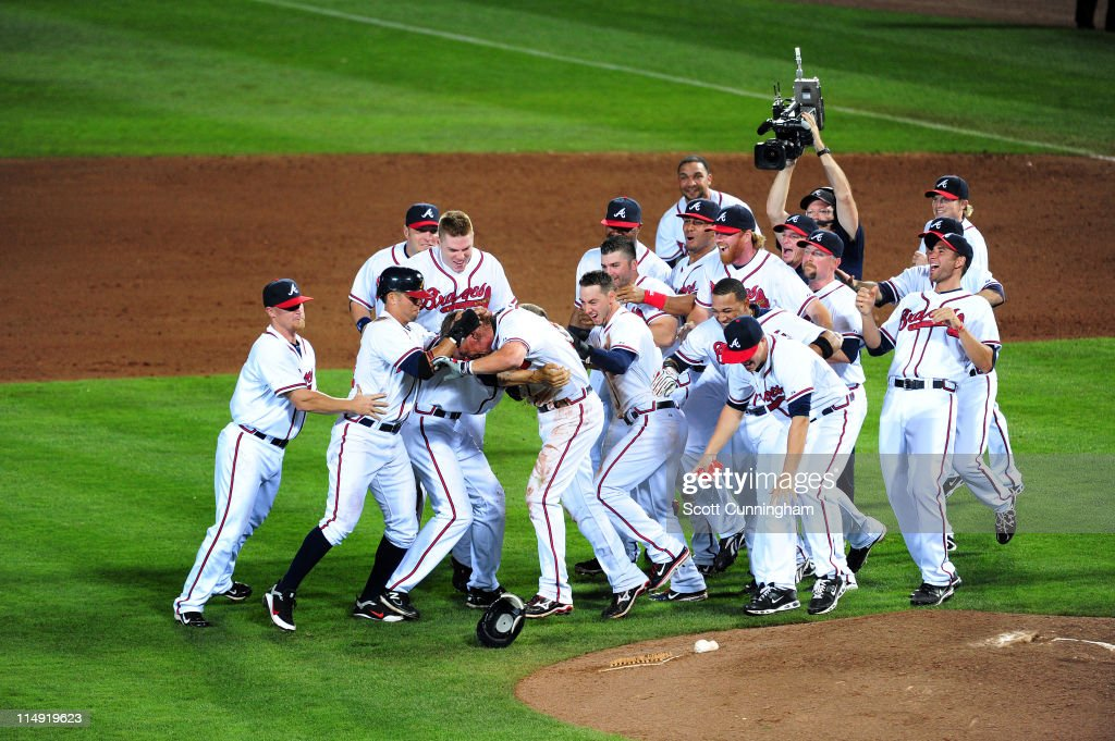 Chipper Jones #10 of the Atlanta Braves is mobbed by teammates after knocking in the winning run in the 12th inning against the Cincinnati Reds at Turner Field on May 28, 2011 in Atlanta, Georgia.