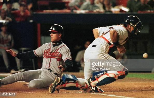 Chipper Jones of the Atlanta Braves slides home safely as New York Mets catcher Mike Piazza bobbles the ball in the first inning of their game 28...