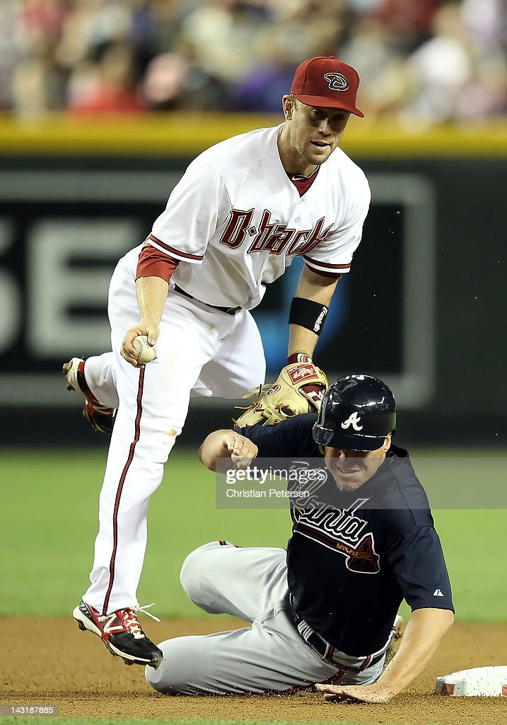Chipper Jones of the Atlanta Braves slides into second base and breaks up a possible double play for infielder Aaron Hill of the Arizona Diamondbacks...