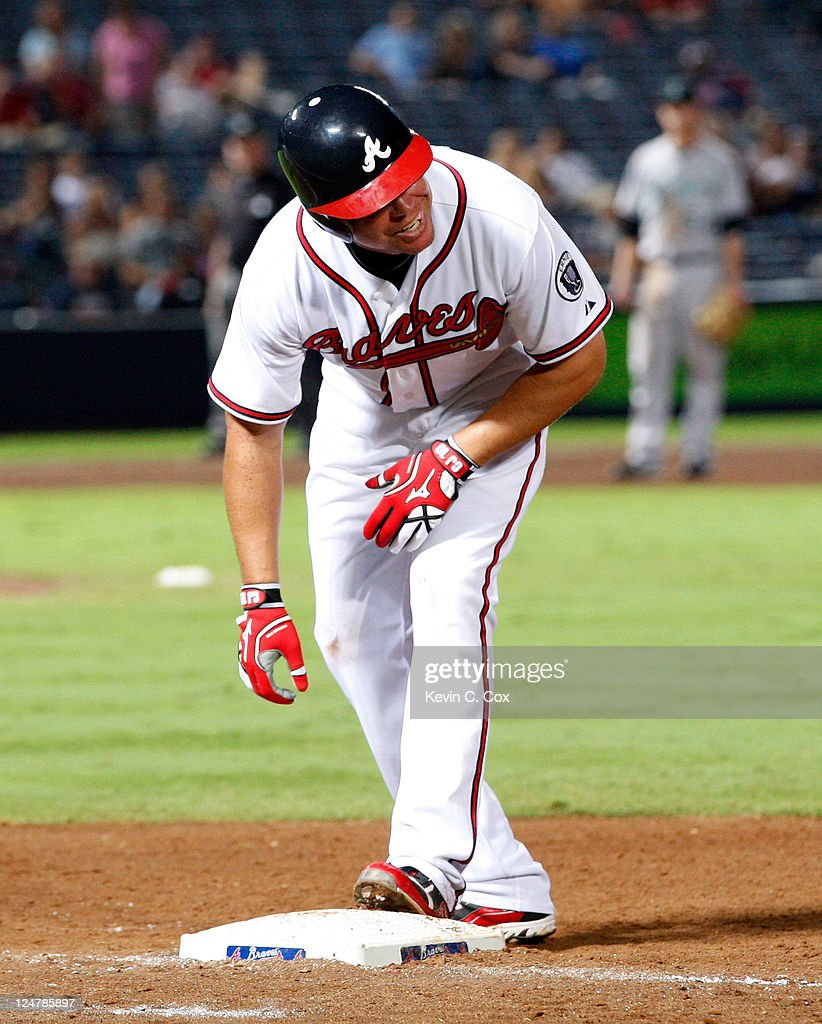 Chipper Jones of the Atlanta Braves stands on first base after beating out a ground ball in a collision at first base against the Gaby Sanchez of the...
