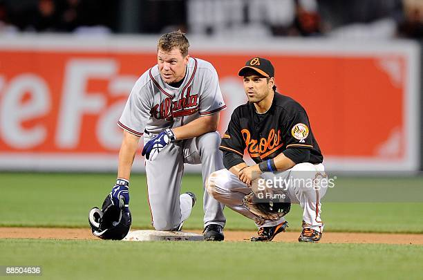 Chipper Jones of the Atlanta Braves talks with Brian Roberts of the Baltimore Orioles during a pitching change at Camden Yards on June 12 2009 in...