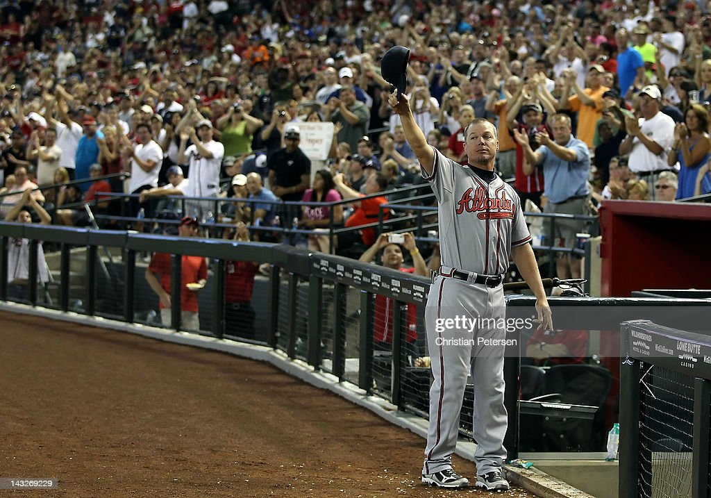 Chipper Jones of the Atlanta Braves waves to the crowd as he is acknowledged for his career accomplishments during the MLB game against the Arizona...