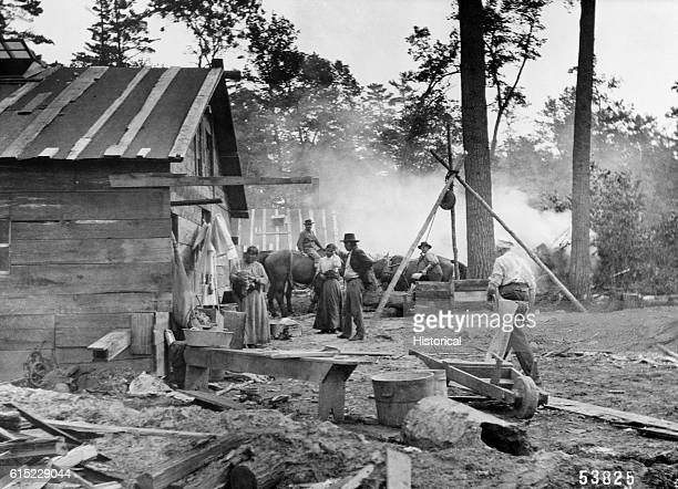 A Chippewa man and two Chippewa women wait outside the kitchen of a logging camp They have brought fish to trade for supplies like flour and tea...