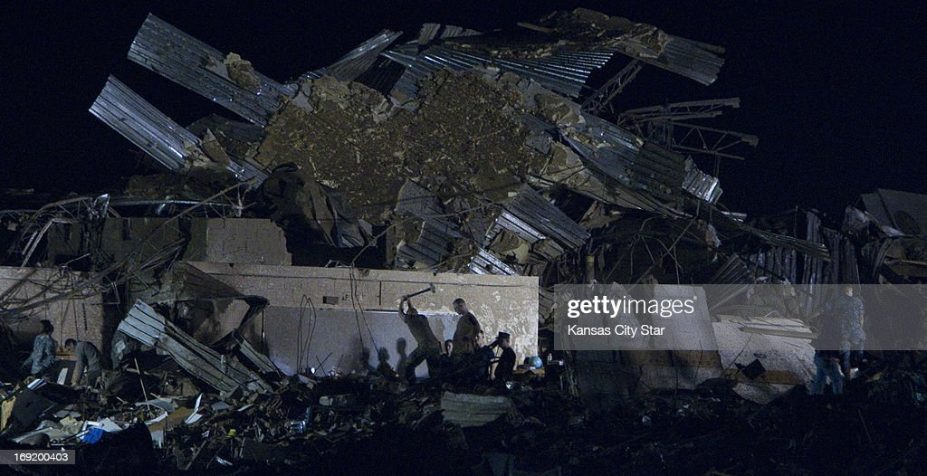 Chipping away at debris with a sledge hammer, rescue personnel comb through the pile of rubble that was once Plaza Towers Elementary School, as emergency crews continued searching for children in the early morning hours on Tuesday, May 21, 2013, in Moore, Oklahoma, after a tornado ripped through part of the town.