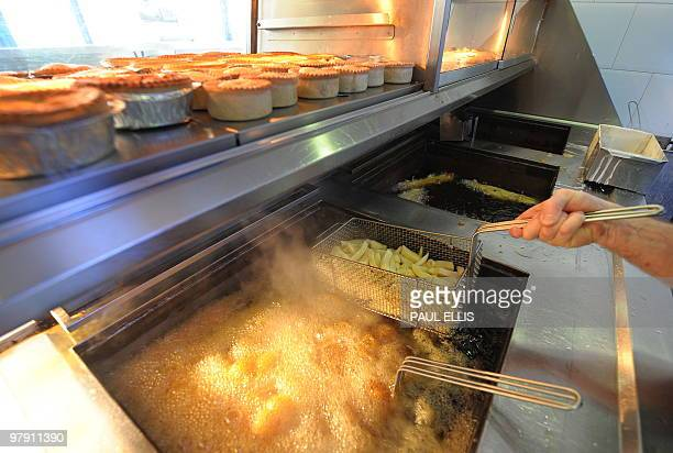 Chips are fried at a Fish and Chip Takeaway in Manchester northwest England on March 10 2010 Whether wrapped in newspaper and eaten with greasy...