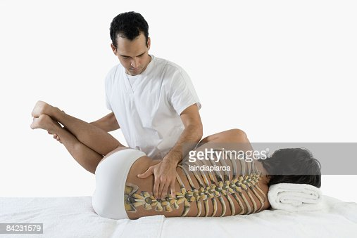 Chiropractor adjusting man's back : Stock Photo
