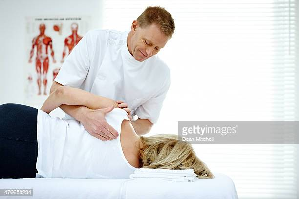 Chiropractor massaging back of female patient