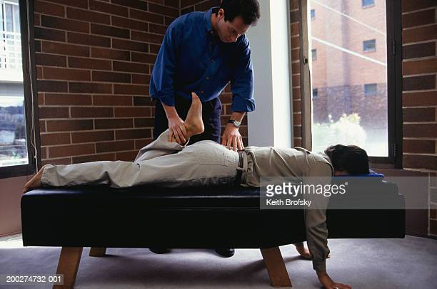 Chiropractor treating patient in clinic