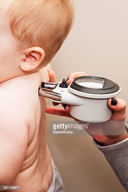 Quiroprático utilizando um medidor para medir a temperatura da coluna ao longo de Criança