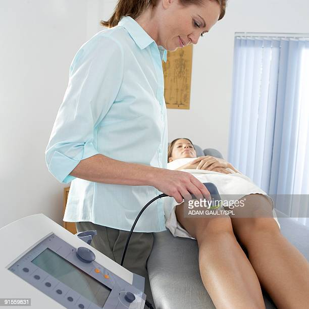 Chiropractor using electrotherapy to treat complaint in patient's knee