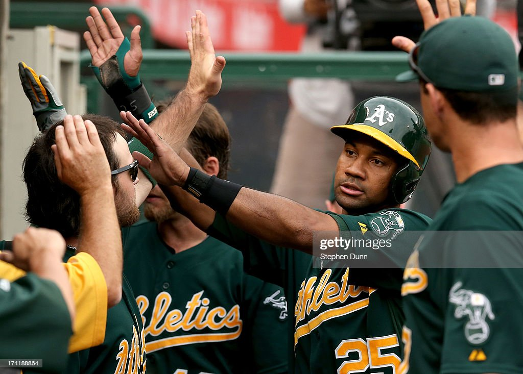 Chirs Young #25 of the Oakland Athletics celebrates in the dugout after scoring a run in the sixth inning against the Los Angeles Angels of Anaheim at Angel Stadium of Anaheim on July 21, 2013 in Anaheim, California.