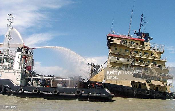 A firefighting Bangladeshi Navy ship helps extinguish a fire onboard the 'Bangla Sourav' tanker in the southern port city of Chittagong 24 June 2006...