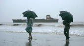 Bangladeshi tourists carry umbrellas as they walk in a squall on a beach on the outskirts of Chittagong 14 May 2007 following a cyclone alart in the...