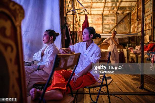 Chiu Chow opera crew members watch a performance from the side of the stage during an event to mark the Hungry Ghost Festival in Hong Kong on...