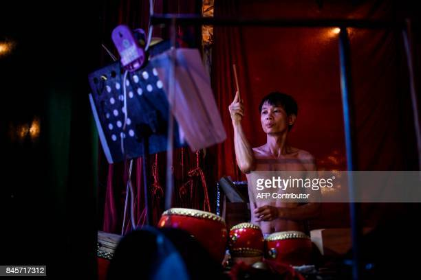 A Chiu Chow opera percussionist performs during an event to mark the Hungry Ghost Festival in Hong Kong on September 11 2017 The festival celebrated...
