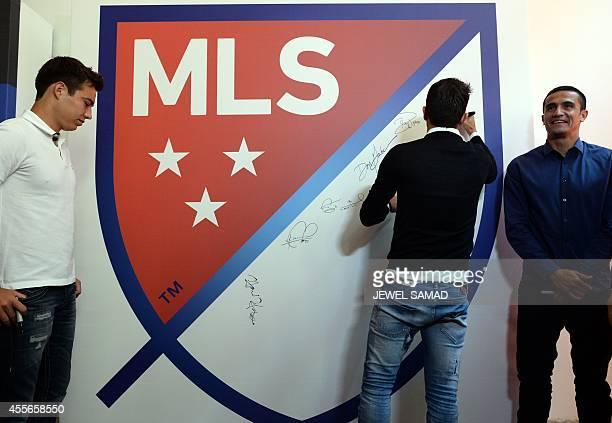 Chivas USA forward Erick Cubo Torres and New York Red Bulls midfielder Tim Cahill look on as New York City Football Club forward David Villa...