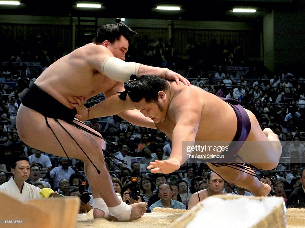 Chiyotairyu (R) pushes out Mongolian yokozuna, sumo grand champion Harumafuji, whose real name is Davaanyamyn Byambadorj to win during day eight of the Grand Sumo Nagoya Tournament at Aichi Prefecture Gymnasium on July 14, 2013 in Nagoya, Aichi, Japan.