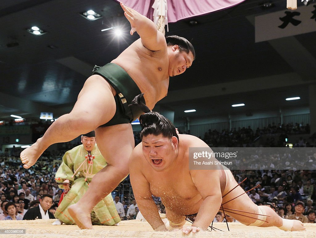 Chiyotairyu (L) throws Jokoryu to win during day one of the Grand Sumo Nagoya Tournament at Aichi Prefecture Gymnasium on July 13, 2014 in Nagoya, Aichi, Japan.