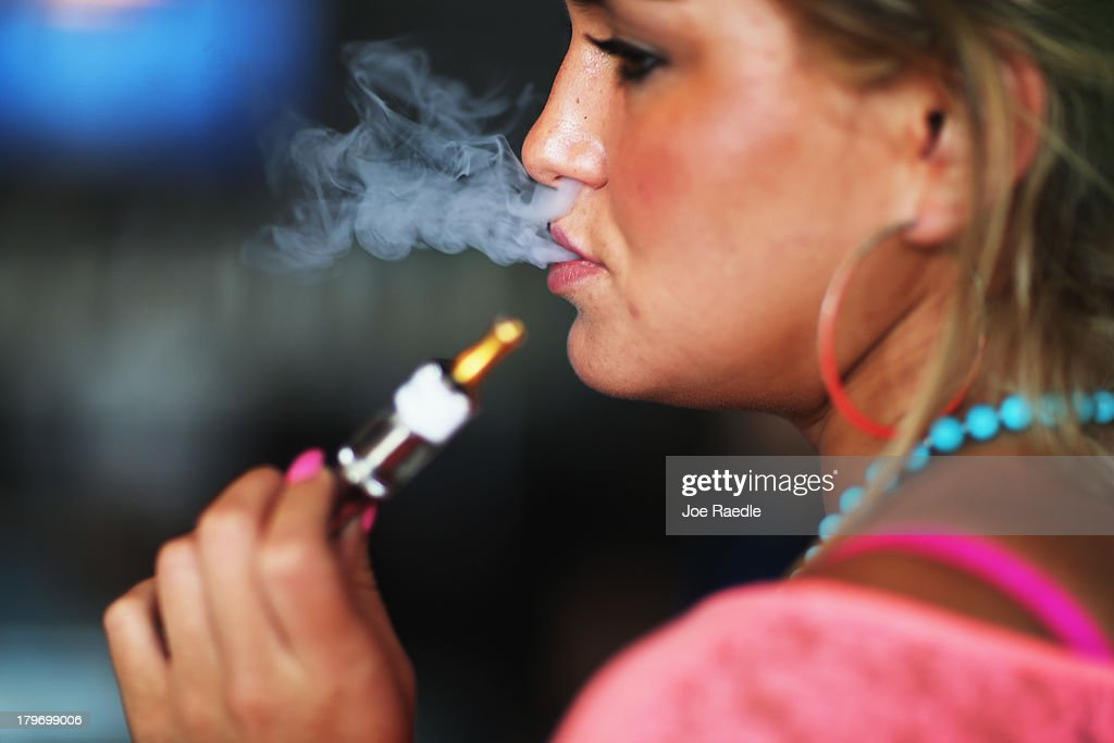 Chloe Lamb enjoys an electronic cigarette at the Vapor Shark store on September 6, 2013 in Miami, Florida. E-cigarette manufacturers have seen a surge in popularity for the battery-powered devices that give users a vapor filled experience with nicotine and other additives, like flavoring.