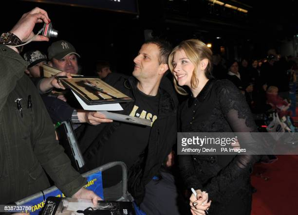 Chloe Moretz poses for photographs as she arrives for the Royal Film Performance 2011 of Hugo at the Odeon Cinema in Leicester Square London