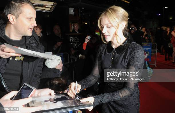Chloe Moretz signs autographs as she arrives for the Royal Film Performance 2011 of Hugo at the Odeon Cinema in Leicester Square London