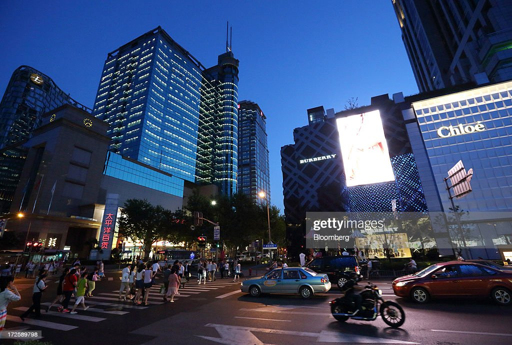 A Chloe store, operated by Cie. Financiere Richemont SA, right, and a Burberry store, operated by Burberry Group Plc, second from right, stand illuminated at night as pedestrians cross a road in Shanghai, China, on Tuesday, July 2, 2013. Banks including Goldman Sachs Group Inc. have pared their growth projections for China this year to 7.4 percent, below the government's 7.5 percent goal disclosed at the March conference at which Li Keqiang became premier. Photographer: Tomohiro Ohsumi/Bloomberg via Getty Images