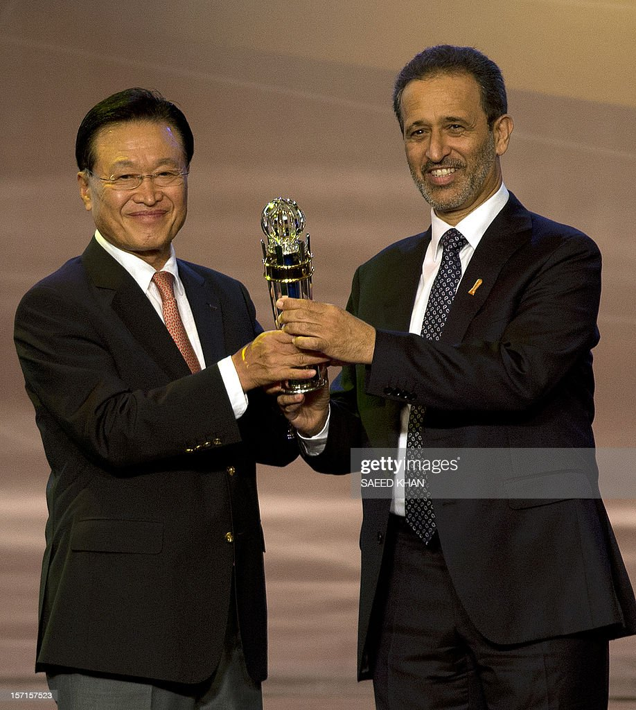 Cho Chung-yun (L), President of South Korea Football Association, receives his award from AFC Vice President Yousuf Yaqoob Yousuf al-Serkal (R) after winning the AFC National Team of the Year for Men award during the Asian Football Confederation award ceremony in Kuala Lumpur on November 29, 2012. AFP PHOTO / Saeed KHAN