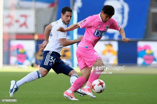 Cho Dong Geon of Sagan Tosu controls the ball under pressure of Milos Degenek of Yokohama FMarinos during the JLeague J1 match between Sagan Tosu and...
