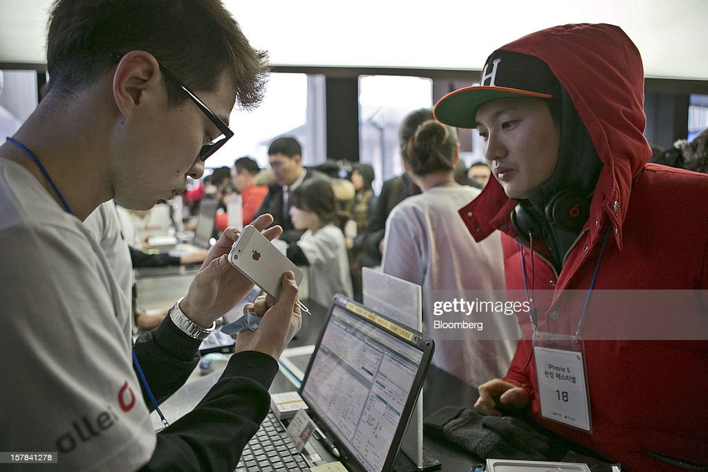 Cho Min-woo, 32, right, purchases an Apple Inc. iPhone 5 at a KT Corp. Olleh brand mobile phone store in Seoul, South Korea, on Friday, Dec. 7, 2012. The iPhone 5 went on sale in South Korea today. Photographer: Jean Chung/Bloomberg via Getty Images