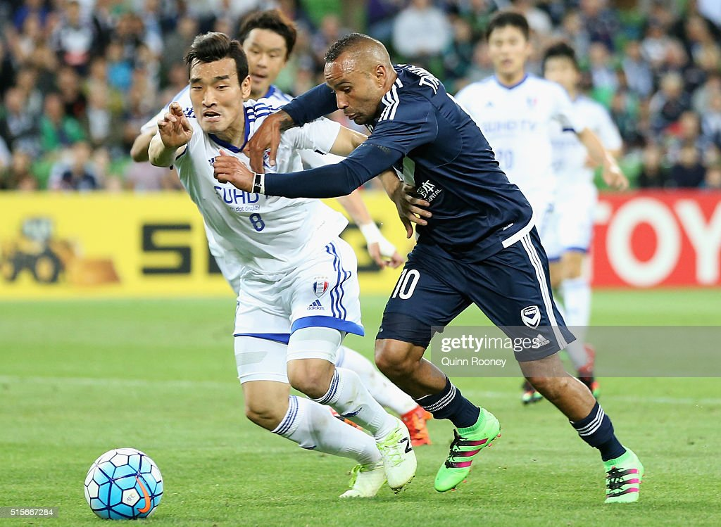 Cho Won Hee of Suwon and Archie Thompson of the Victory compete for the ball during the AFC Champions League match between the Melbourne Victory and...
