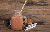Chocolate and cocoa mixed with milk smoothies on wooden floor.