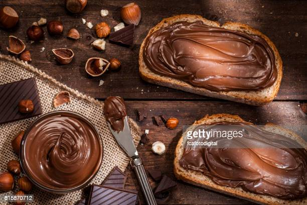 Chocolate and hazelnut spread on bread slices shot on rustic wooden table