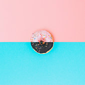 Art collage of chocolate and pink donuts with topping. Minimalism and surrealism