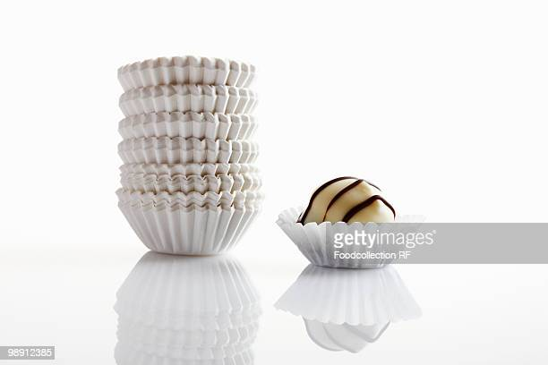 Chocolate and stack of paper cases on white background