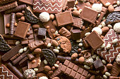 Chocolate background. Many pieces of chocolate, candies, cookies, biscuits, cakes and other sweets. Milk chocolate and dark chocolate. coconut candy