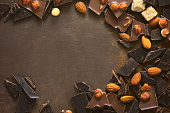 Various types of chocolate pieces crushed on a dark surface, chocolate background with a space for a text, view from above