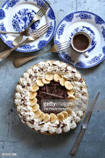 Chocolate banana cream pie on a pan with blue plates and cutlery.Top view