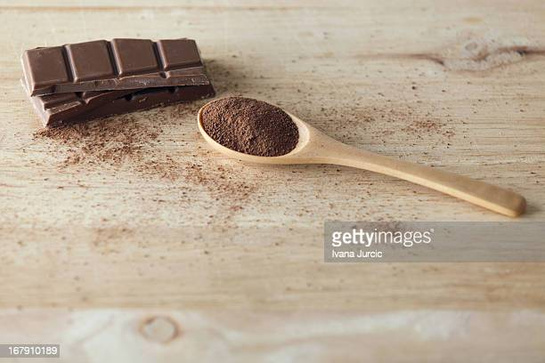 Chocolate Bar and Cocoa Powder on Wooden Surface