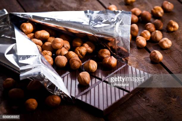 Chocolate bar and hazelnuts on rustic wood table