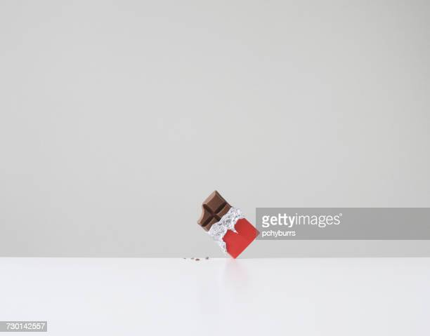 Chocolate bar with missing bite and chocolate crumbs on table