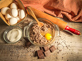 Raw chocolate cake batter surrounded by eggs, sugar, chocolate and sprinkles. Shot from above with a natural rustic color and texture in horizontal orientation.