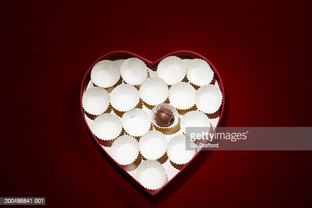 Chocolate bon-bon and empty wrappers in heart shaped box