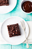 Chocolate brownie, cake on a white plate on a turquoise wooden background