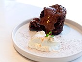 chocolate brownie lava cake and melted chocolate served with whip cream on white round plate on white marble table