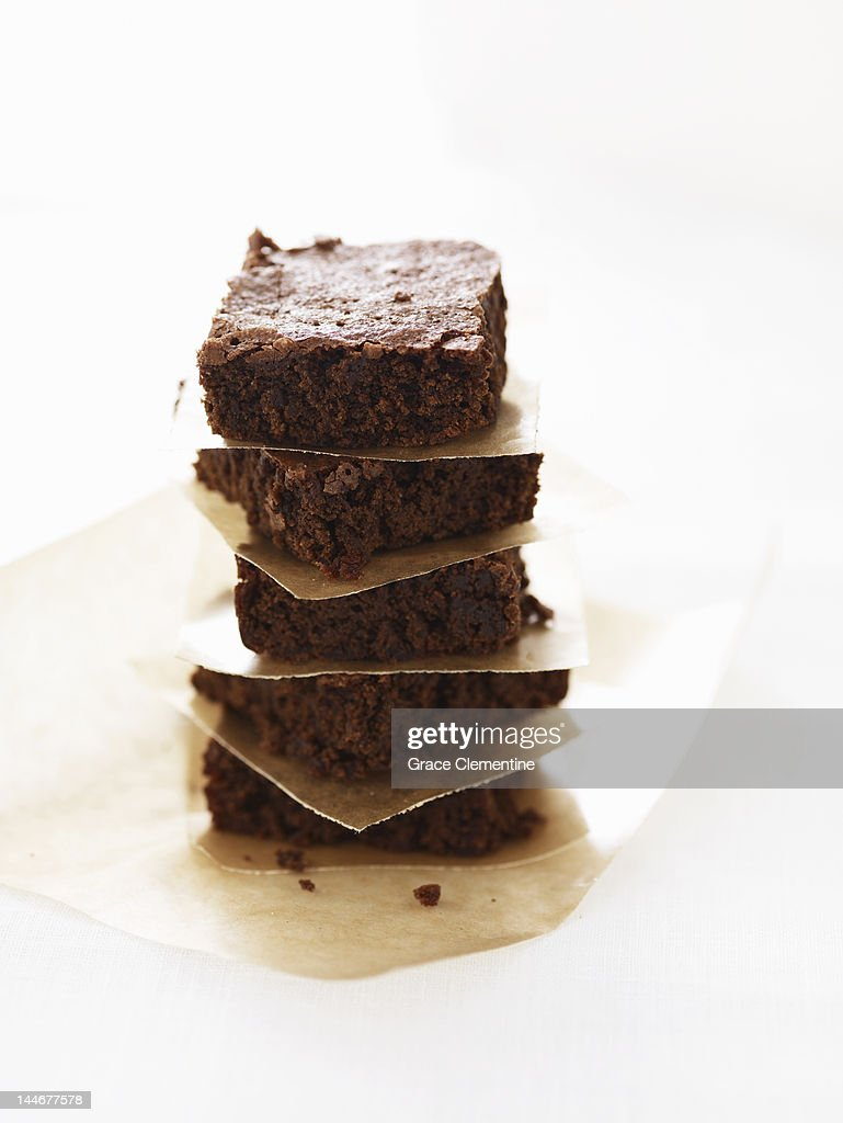 Chocolate brownies in stack with parchment paper c : Stock Photo