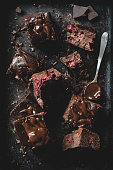 Chocolate cherry brownies decorated with melted chocolate on dark background. Table top view