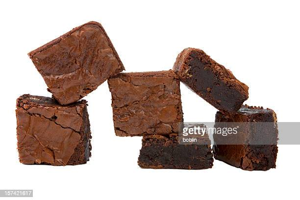 Chocolate brownies stacked in front of a white background