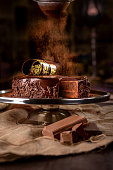 Chocolate cake on a platter in a bakery on dark background