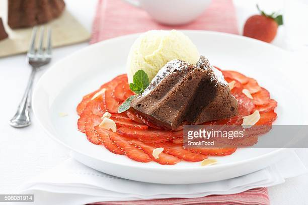 Chocolate cake on strawberry carpaccio with vanilla ice cream
