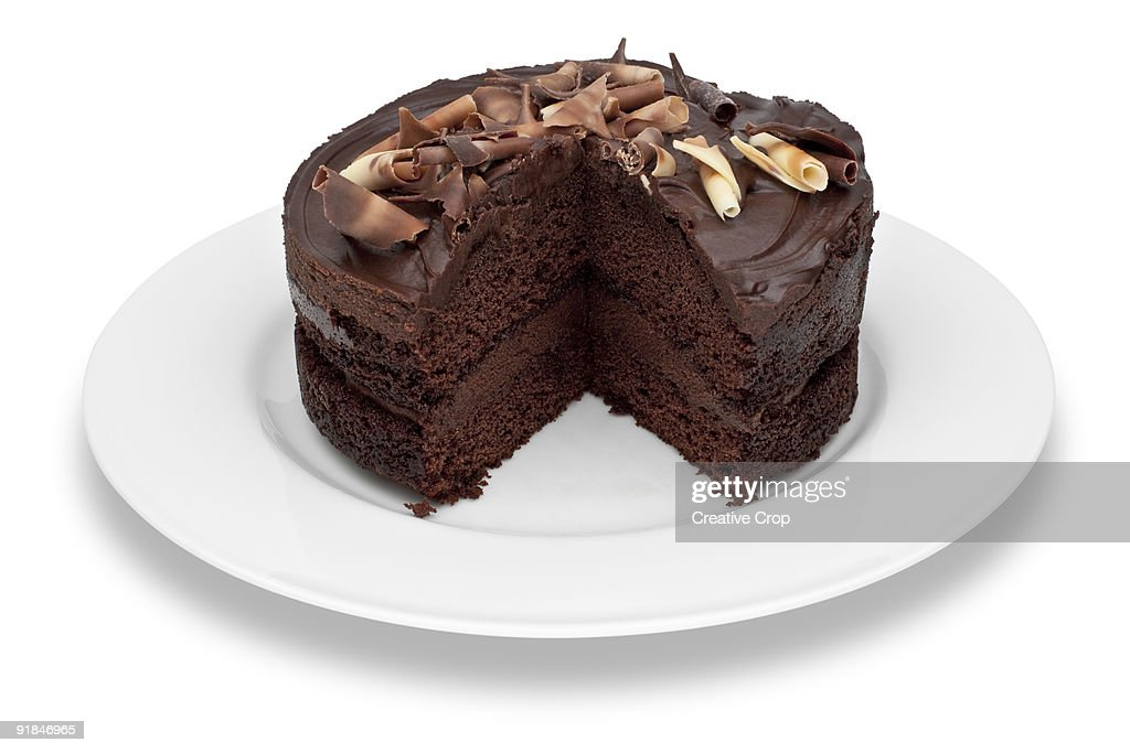 Chocolate cake on white plate, with slices missing : Stock Photo